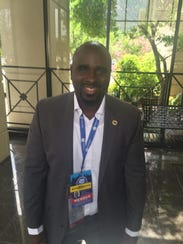 Mayo Makinde wears his convention credential with Black