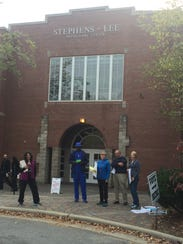 Democratic poll workers offer sample ballots outside