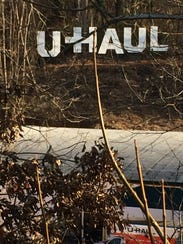 The large, metal U-Haul sign behind the Swannanoa River
