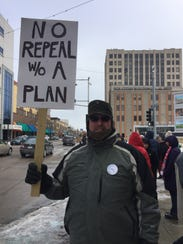 Greenville's Ken McIntosh holds a sign in support of