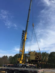 A crane is used to lift the 32,000 pound anti-aircraft