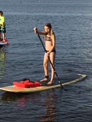 A young girl enjoys herself paddle boarding. Paddle