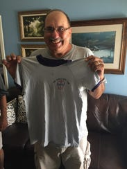 Harold Lopez holds up his old Boys' Club T-Shirt from