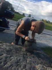 Derek Vodika, 11, of Fremont chips dirt off of a bowling