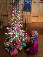 Sally Karioth poses with a tree she made for Habitat