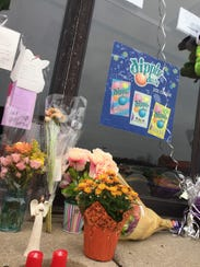 Flowers, cards and balloons sit outside Jump N Jam