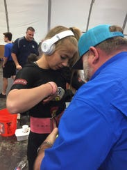 Calvary powerlifter Kailey Brookshire, a 2017 Times Sports Award honoree, gets assistance from her father before a lift Saturday at the Calvary meet.
