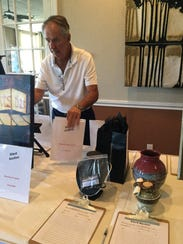 Ed Douglas sets up silent auction items at last year's