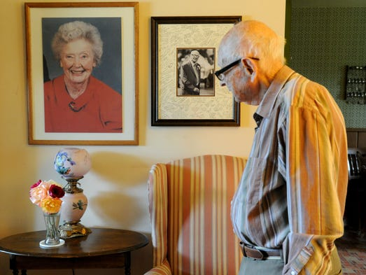 Carl Greenfield, 100, looks at photos of himself and