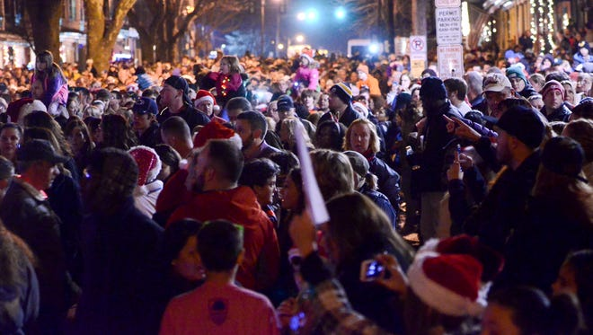 "People fill the 400 block of Chestnut Street on Dec. 21, 2013, in West Reading, Pa., where thousands of people came out to sing carols in front of the home of Delaney ""Laney"" Brown, 8."