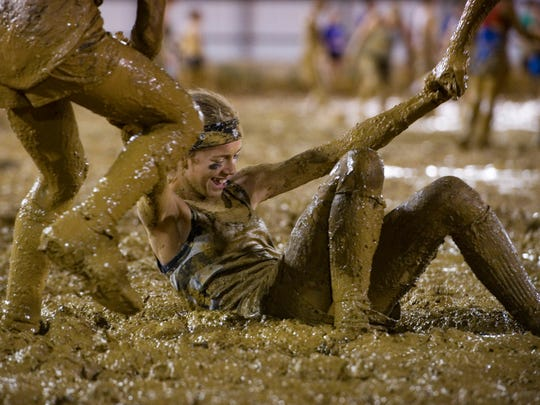 Hannah Tolley, 13, is helped to her feet after making a diving attempt at the muddy volleyball at the Warrick County 4-H Fair Mud Volleyball Contest during a previous year's fair.