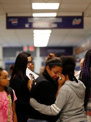 Seventh grader Raylea Lewis (left) wipes tears from