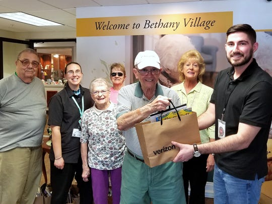 Verizon TCC Elmira Manager Nick Spence, right, presents gift bags to Bethany Village residents in honor of National Nursing Home Week.
