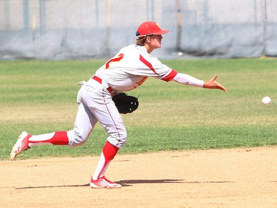Travis Moniot, shortstop for Palm Desert High School, flicks the ball to second base to start a double play during a game at Palm Springs High on May 9, 2014.