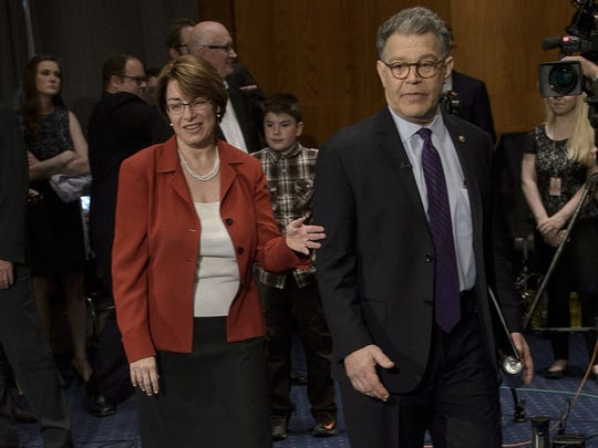 Senator Amy Klobuchar and Senator Al Franken both sit