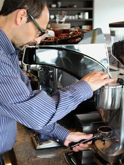Larry Fisher grinds beans at Eagle Specialty Coffee in Eatontown.