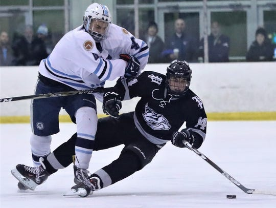Livonia Stevenson defenseman Jake Beaune (4) delivers a check against Plymouth's Luke Kaledas (14).