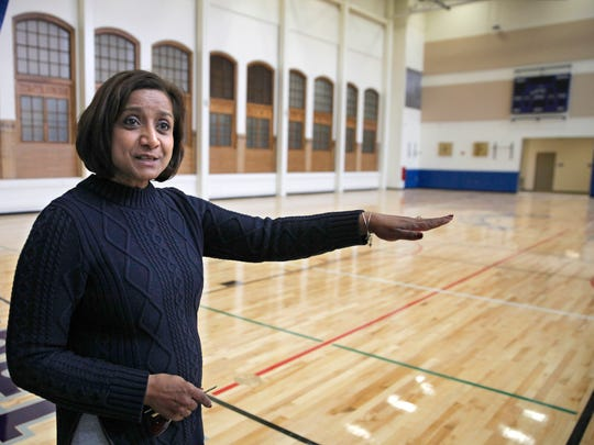 World of Inquiry School principal Sheela Webster shows off the new gym that features original woodwork as part of the new design.