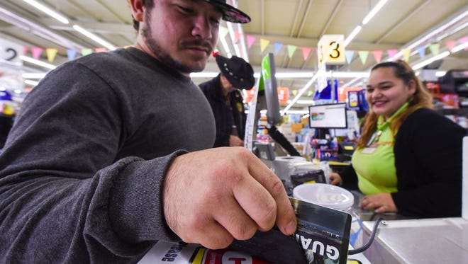 Mangilao resident Edward Pangelinan inserts a Guam Quest card into a credit card terminal as Day Supervisor Tasha Cabrera observes at the Day Buy Day supermarket in Piti on Friday, Dec. 5, 2018.