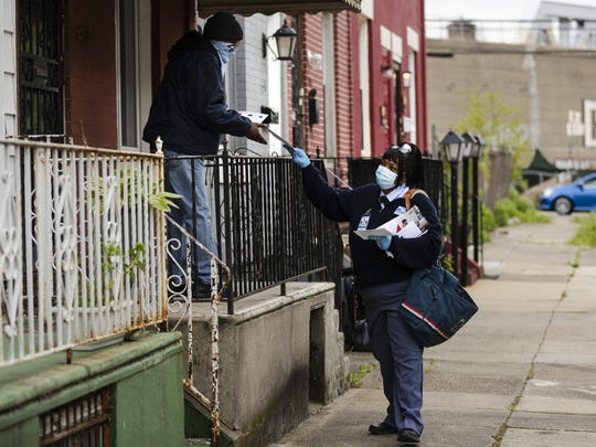 """United States Postal Service carrier Henrietta Dixon delivers mail to Alvin Fields in Philadelphia earlier this month. Fields called Dixon """"absolutely wonderful."""""""