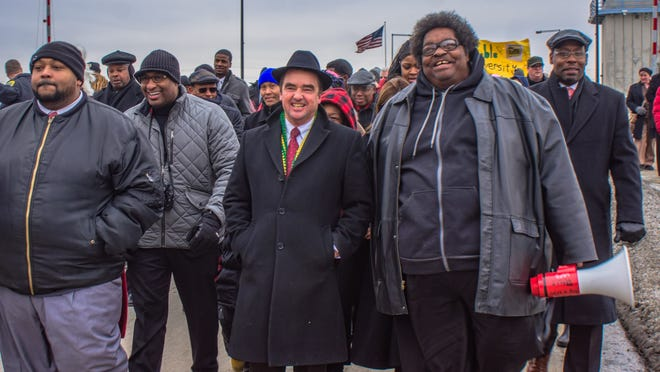Green Bay Mayor Jim Schmitt joins The Rev. L.C. Green and other marchers downtown Monday to honor Martin Luther King, Jr.