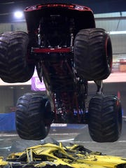 A monster truck flies through the air during Friday's Kicker Monster Truck Mania event at the McGee Park Coliseum.