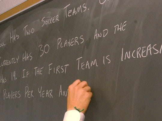 A math question is posted on a chalkboard for students preparing for the ISTEP test.