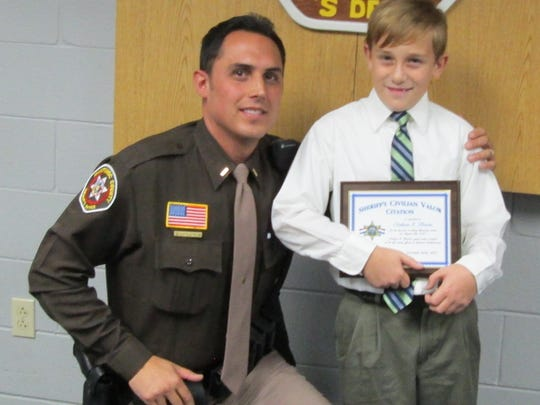 Manitowoc County Sheriff's Office Lt. Sean Littlefield with Nathan Hawke, 10, of Two Rivers, who as honored by the department for his efforts in helping to save his 6-year-old cousin in August.