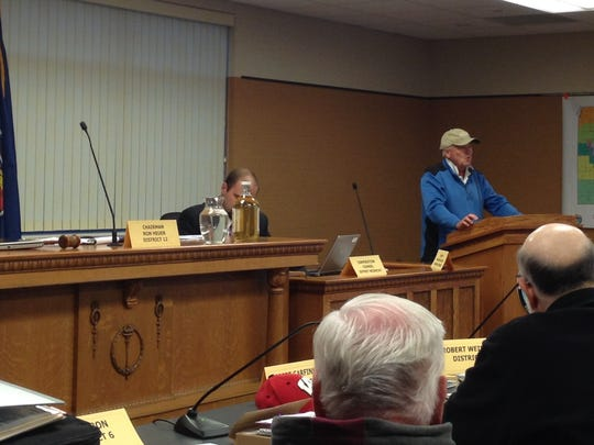 Dick Swanson advocates for the passage of the Kewaunee County public health and groundwater protection ordinance during the Sept. 23 County Board meeting. He placed two jugs of water, one brown and one clear (not necessarily from Kewaunee County wells), in front of Chairman Ron Heuer.