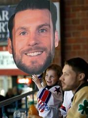 Amerks fan Lyric Roy, 6, of Henrietta holds a face cutout of Nathan Paetsch during the home game against the Syracuse Crunch at the Blue Cross Arena at the War Memorial in April 2018. Paetsch's volunteer work in the community has earned him four McCulloch trophies and two Amerks AHL Man of Year awards.