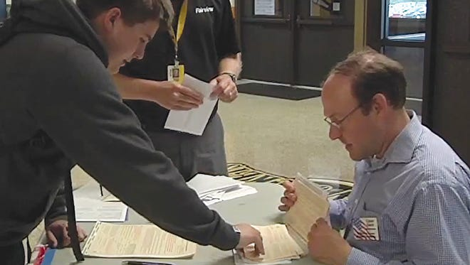 Chad Gray, administrator of elections for Williamson County (right) assists Fairview High School student with voter registration information.