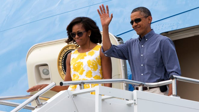 President Obama and first lady Michelle Obama wave as they arrive Aug. 10  in Cape Cod, Mass., to fly via helicopter to begin their family vacation in Martha's Vineyard.