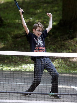 Thirteen-year-old J.J. Laboucane, of Massillon, celebrates a point while playing pickleball with his father, Joe Laboucane, at the Lincoln Park in Massillon.