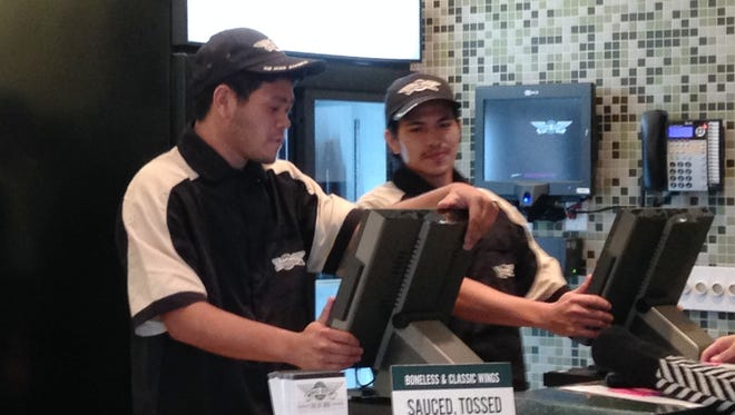 """Employees at Wingstop practice taking orders at the counter Monday night while the kitchen crew prepares special """"Wingdrop"""" delivery orders."""