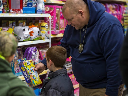An officer helps a young boy with finding presents