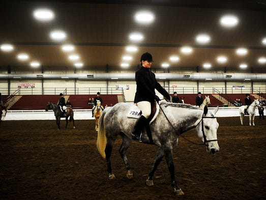 Kristie Earl, of Sioux Falls, walks out of the arena after placing first in the Hunter Under Saddle class during the 2014 HorsePower Benefit Horse Show on Saturday, April 26, 2014, at the W.H. Lyons Fairgrounds in Sioux Falls. (Joe Ahlquist / Argus Leader)