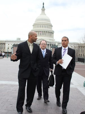 This April 2, 2014, file photo shows former Northwestern University football quarterback Kain Colter, right, Ramogi Huma, founder and President of the National College Players Association left, and Tim Waters, Political Director of the US Workers on Capitol Hill in Washington.
