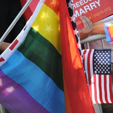 American and Rainbow flags are seen at a rally celebrating the Supreme Court rulings regarding same-sex marriage
