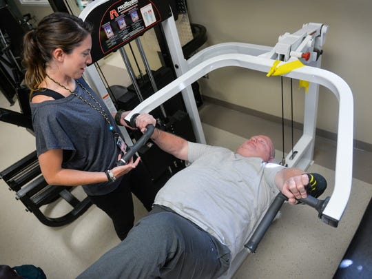Marine Corps veteran and stroke survivor Randy Falknor bench presses as much as 240 pounds Wednesday, July 20, under the watchful eye of his recreational therapist, Leah Egan, at the St. Cloud VA Health Care System gym.