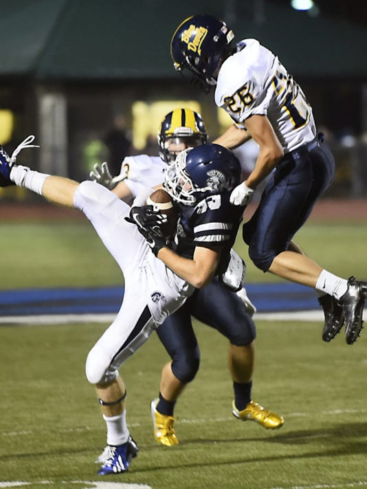 Chambersburg's Clay Myers (33) catches a deep pass against Liam Okal, right, of Greencastle-Antrim, on Friday. Myers finshed with two catches for 48 yards, but the Trojans lost, 32-29 in overtime.