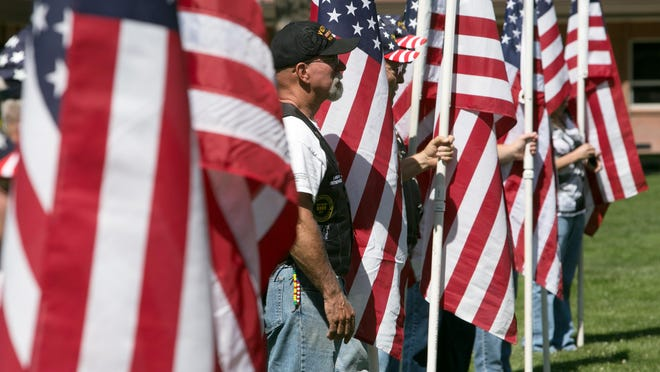 Members of the Patriot Guard Riders of Southern Utah stand holding American flags during the Memorial Day service at the Washington City Veteran's Park, May 27, 2013.