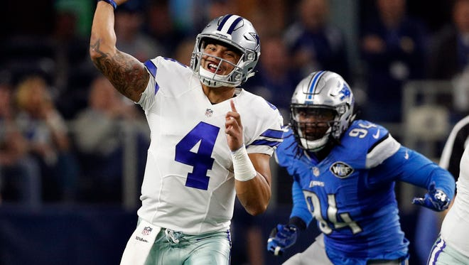 Cowboys quarterback Dak Prescott throws a pass as Lions defensive end Ziggy Ansah pressures him Monday, Dec. 26, 2016 in Arlington, Texas.