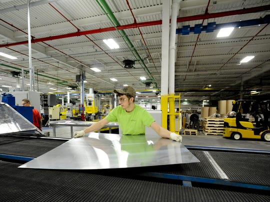In this file photo, Damien Balde of Kiel inspects freshly cut custom-sized sheets of metal at Skana Aluminum in Manitowoc.