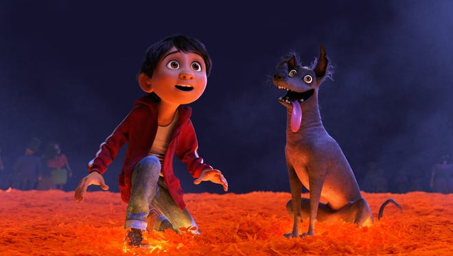 "Miguel (voiced by Anthony Gonzalez) and his loyal dog Dante cross over into the Land of the Dead via a bridge made of marigold petals in ""Coco."""