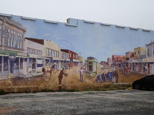 An old-time scene is painted on a building at Chadbourne and Concho streets in downtown San Angelo.
