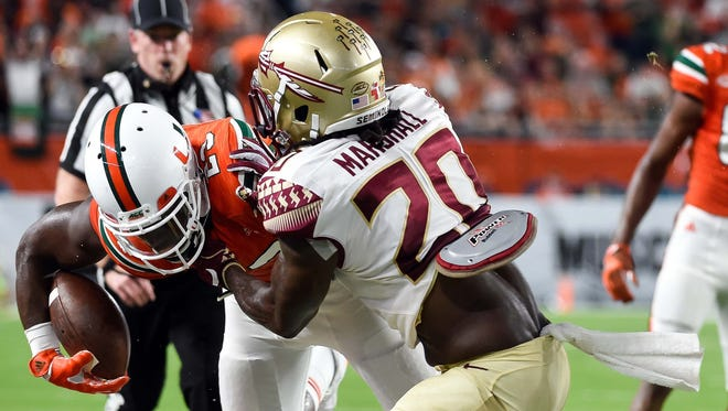 Miami Hurricanes tight end Christopher Herndon IV (23) is tackled by Florida State Seminoles defensive back Trey Marshall (20). Marshall finished with three tackles.