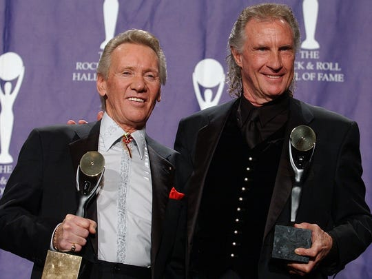 Righteous Brothers Bill Medley, right, and Bobby Hatfield pose at their Rock and Roll Hall of Fame induction ceremony in March 2003. Hatfield died later that year.
