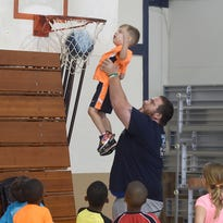 Camp assistant Matt Standiford hoists a camper for a slam dunk Tuesday at the youth basketball camp at Westminster Christian Academy.