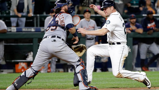 Seattle Mariners' Adam Lind, right, scores the winning run as Detroit Tigers catcher Jarrod Saltalamacchia waits for the throw in the 15th inning. Seattle won 6-5.
