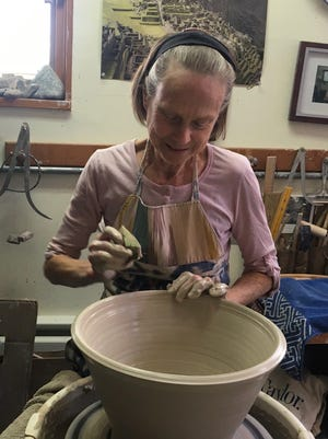 Annie Schliffer, head potter with the Rochester Folk Art Guild, is at work in the workshop at the guild's Middlesex home. {PHOTO PROVIDED]